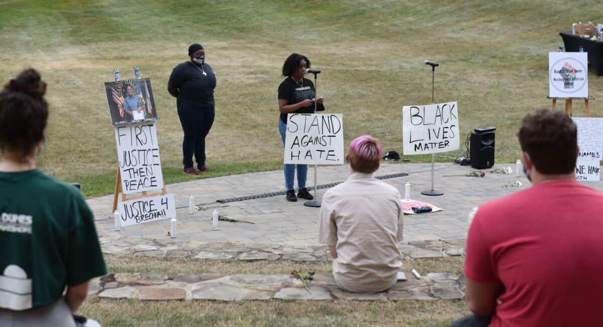 W&J BSU President Tamia Mickens '21 speaks surrounded by signs promoting racial justice at the BSU's Celebration of Black Life, held in the amphitheater on W&J's campus.