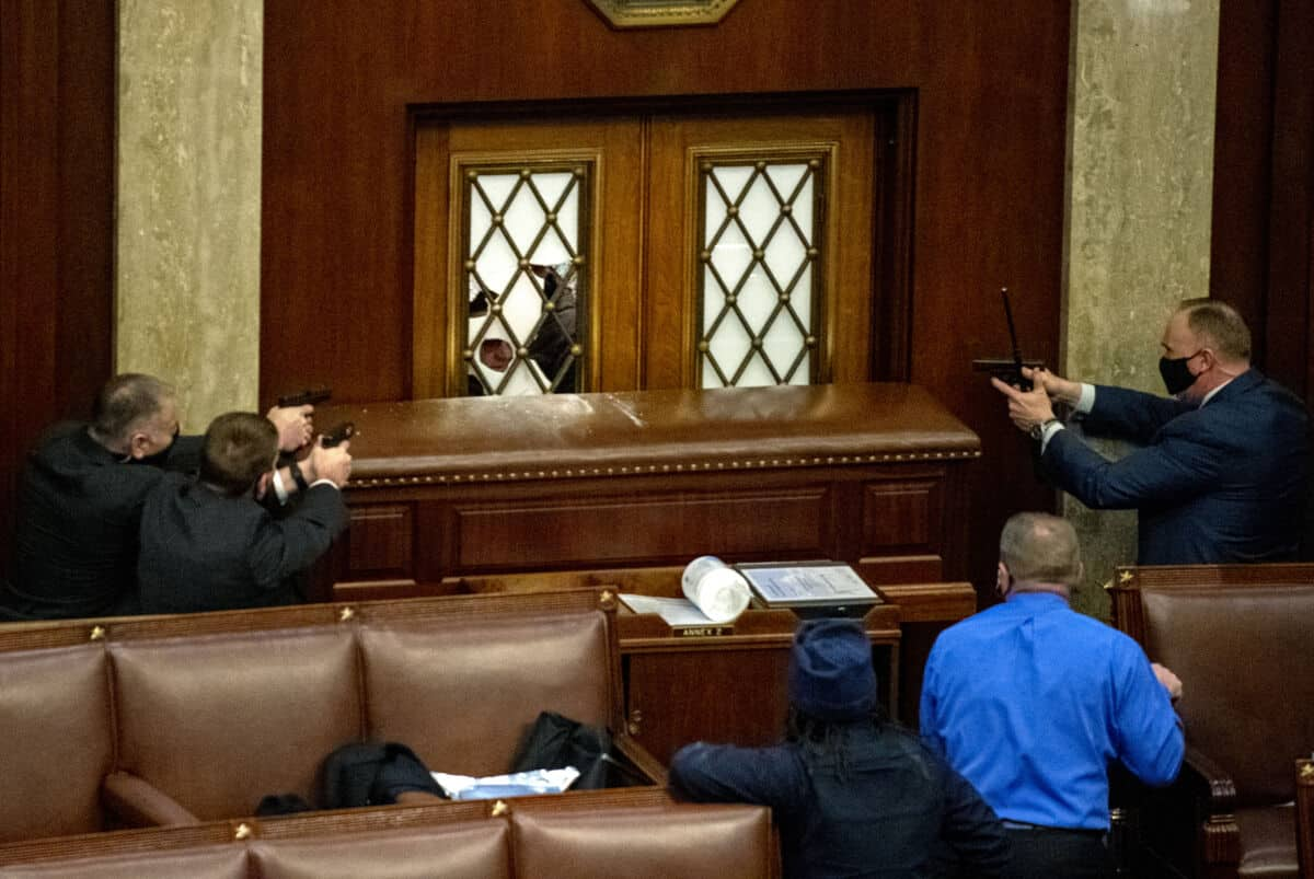 A photograph captured by W&J graduate photographer Pat Benic shows plain clothes Capitol Police point their guns at rioters who had broken the glass of the main door of the House Chamber that was reinforced with a large piece of furniture at the U.S. Capitol in Washington, DC on Wednesday, January 6, 2021.