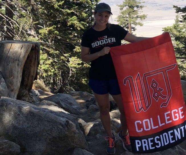 Brianna McGowan stops on a hike to pose with a W&J flag.