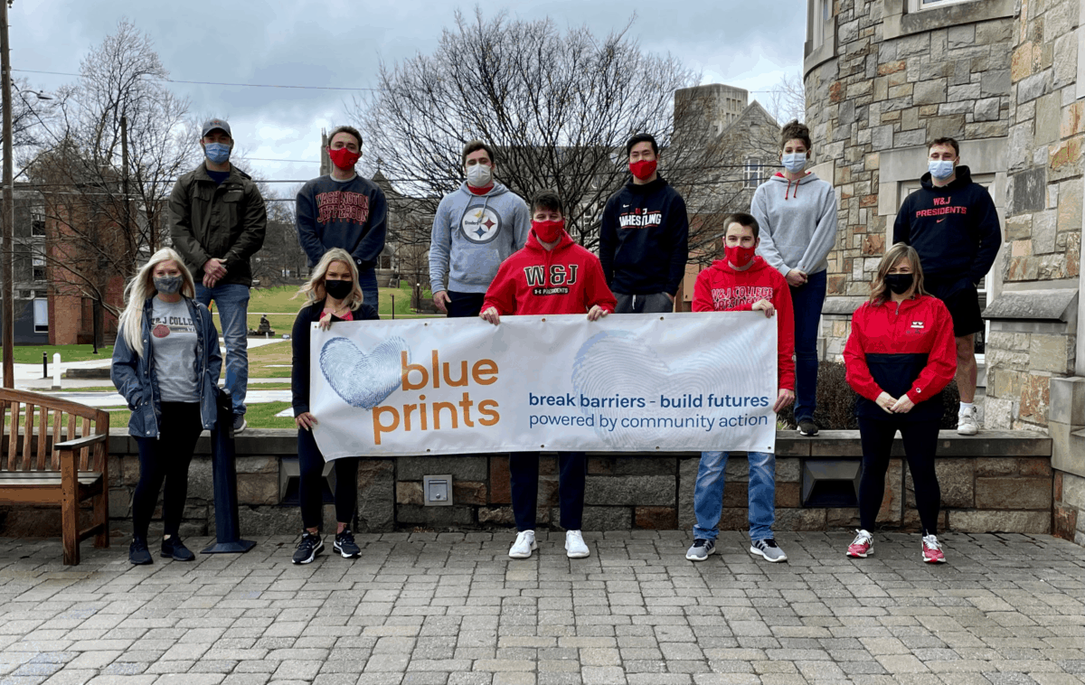 Student participants in the VITA tax program pose with a banner for Blue Prints, the organization through which they are offering tax services.
