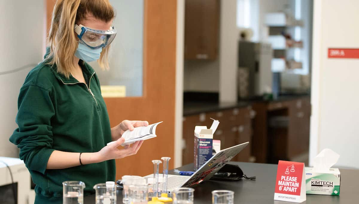 A student wearing goggles and a mask stands by a desk in a science lab with beakers in front of her.