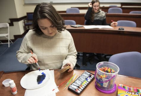 Students in Coloring Club during a December meeting paint and color.
