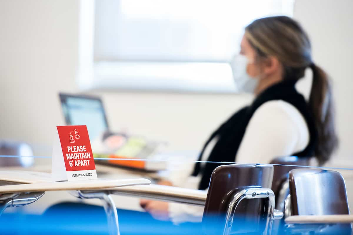 A student sits at her desk on her laptop in the background. In the foreground is a sign that reads
