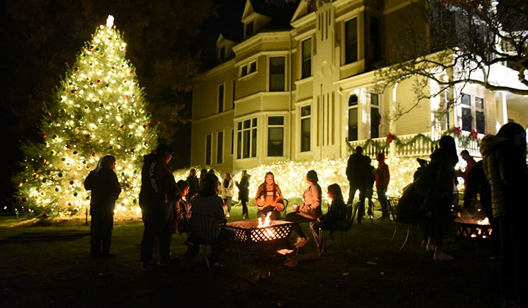 Students gather outside of the President's House during the annual tree lighting ceremony at Washington & Jefferson College.