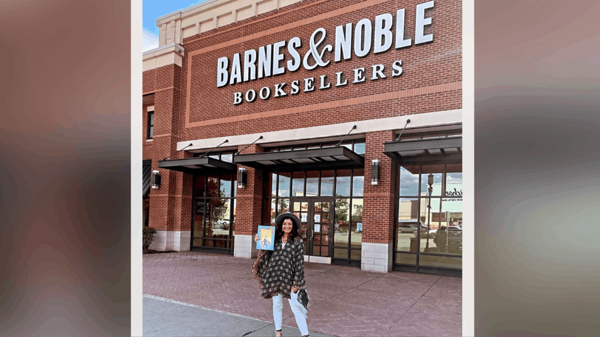 Jacqueline Manina poses in front of a Barnes and Noble store holding her book.