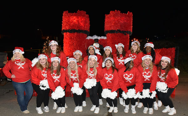 W&J Cheerleaders pose in front of the parade float students put together for the Washington Holiday Parade.