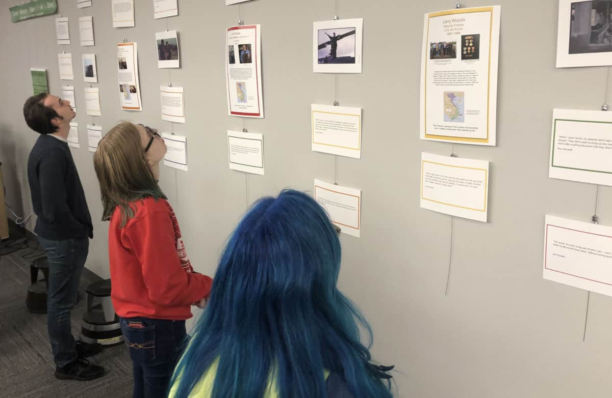 """Students look at the exhibit """"Ever Veteran Has A Story"""" based on student interviews with Vietnam Veterans in Clark Family Library."""