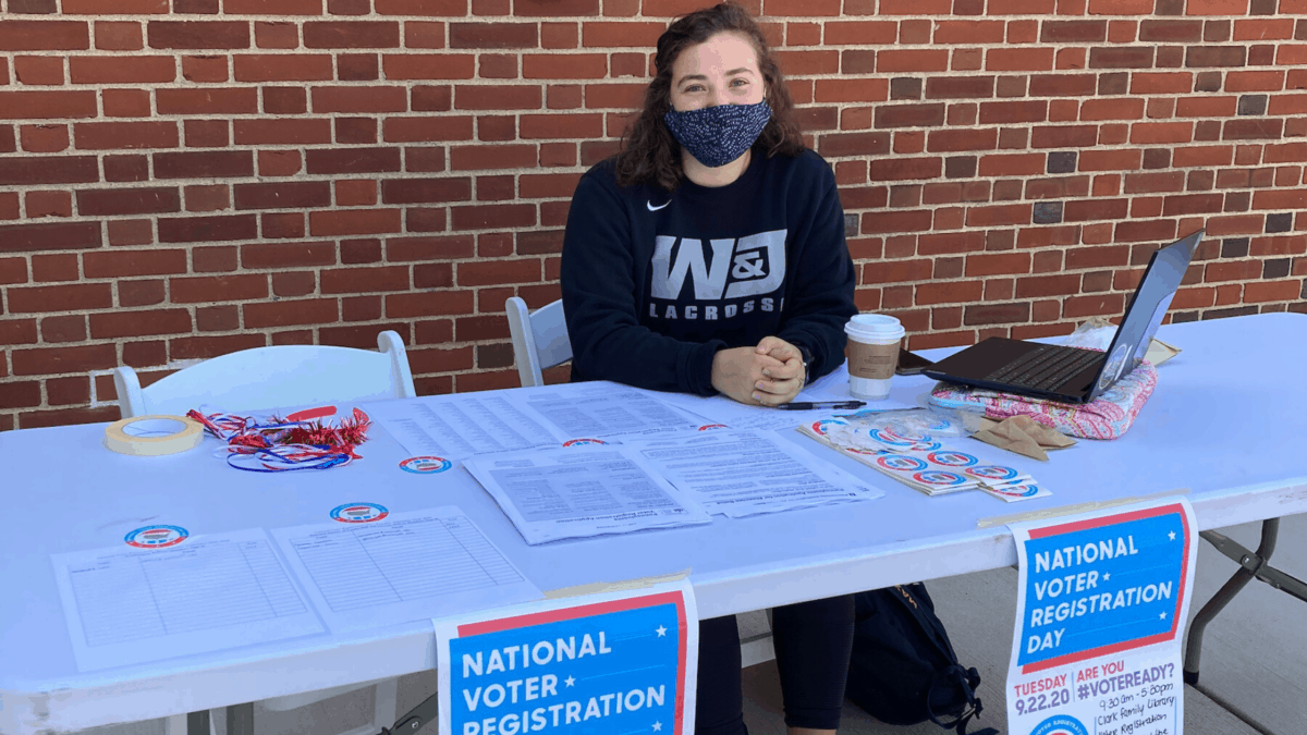A student volunteer with the Student Voting Coalition sits at a table outside of Clark Family Library with voter registration materials.